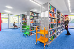 Library with modern shelves. Light library interior with modern shelves and colorful trolley Stock Photos