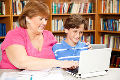 Library - Mother Son. Mom or teacher working with a school boy on the computer in the library stock images