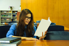 Library. Portrait of asia student with open book reading it in university library Stock Photos