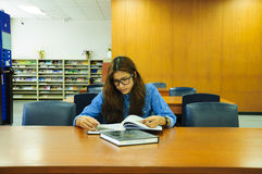 Library. Portrait of asia student with open book reading it in university library Royalty Free Stock Photo