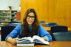 Library. Portrait of asia student with open book reading it in university library Royalty Free Stock Photos