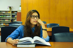 Library. Portrait of asia student with open book reading it in university library Royalty Free Stock Images