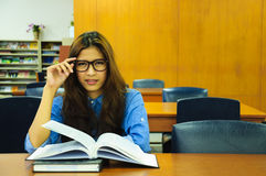 Library. Portrait of asia student with open book reading it in university library Royalty Free Stock Photography