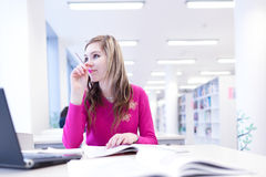 In the library - pretty female student Stock Photo