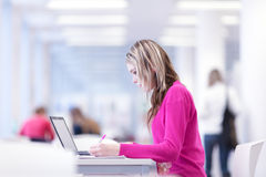 In the library - pretty female student Stock Photography