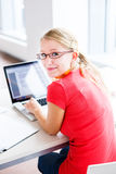 In the library - pretty, female student with books and laptop Royalty Free Stock Photography