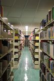 Library. A quiet section of a university library with steel shelves full of various books Royalty Free Stock Images
