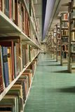 Library. A quiet section of a university library with steel shelves full of various books Royalty Free Stock Photography