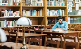 The Library Reading. Concentrated awesome bearded student sitting down on chair at the library desk with books Royalty Free Stock Photography