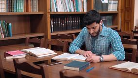 The Library Reading. Concentrated student sitting down on chair at the library desk, young man with wavy black hair putting on white headphones, starts working stock footage