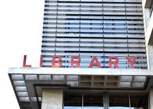 Red Library Sign. `LIBRARY` in red letters set against a modern building Stock Photos