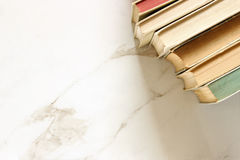 Library shelves. Stack of vintage books on marble desk. Copy space Stock Images