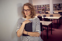 In the library, student girl or young woman with book Royalty Free Stock Photography