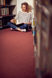 In the library, student girl or young woman with books Royalty Free Stock Photos