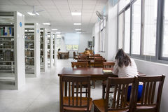 Library study. Young students study in a library with lots of  books on shelves Stock Photo