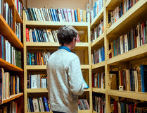 Library visitor stands in front of shelves with books Stock Images