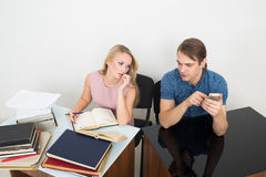 Library. woman looking for information in books. Office. Girl with books. The men speaks on the phone Royalty Free Stock Photography