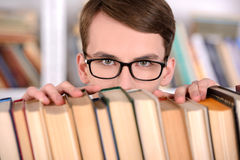 Library. Young male student selecting a book from a library shelf, high school Royalty Free Stock Photos