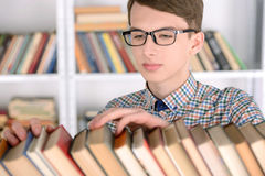 Library. Young male student selecting a book from a library shelf, high school Royalty Free Stock Photography