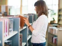 Libreria di Choosing Book In dello studente Fotografie Stock