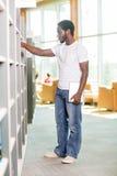 Libreria di Selecting Book In dello studente maschio Immagine Stock Libera da Diritti