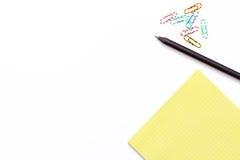 Libreta amarilla, pluma negra y clip de papel colorido en el fondo blanco Concepto de trabajo mínimo para la oficina, escuela, un fotografía de archivo