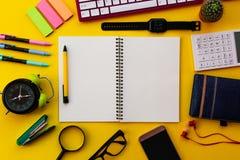 Libreta blanca en blanco con la oficina y los accesorios personales aislados en fondo amarillo imagen de archivo