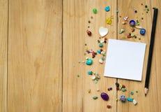 Libreta blanca en la madera con el texto vacío de la goma del espacio usando el papel pintado o el fondo para la nota Imagenes de archivo