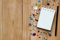 Libreta blanca en la madera con el texto vacío de la goma del espacio usando el papel pintado o el fondo para la nota Foto de archivo libre de regalías