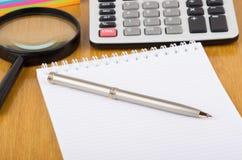 Libreta, calculadora electrónica, pluma y lupa Imagen de archivo