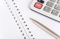 Libreta, calculadora y pluma Foto de archivo libre de regalías