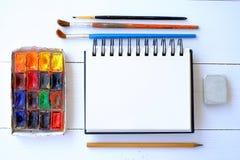 Libreta, cepillos y pintura en la tabla imagen de archivo