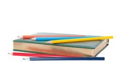Libreta con el deletreado del oro y los lápices coloreados Imagen de archivo libre de regalías
