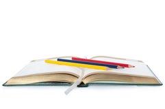 Libreta con el deletreado del oro y los lápices coloreados Imagen de archivo