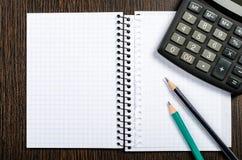 Libreta con el lápiz y la calculadora Fotos de archivo