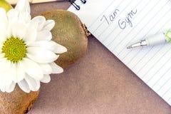 Libreta con la cita del gimnasio escrita en ella al lado de la fruta de kiwi y Foto de archivo libre de regalías