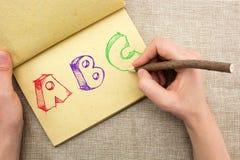 Libreta con la mano que dibuja las letras coloridas de ABC Fotografía de archivo libre de regalías