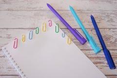 Libreta con la página en blanco y plumas coloridas del grapa y azules en una tabla de madera Mofa para arriba imagen de archivo libre de regalías