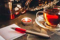 Libreta con la taza de té en la tabla Imagen de archivo libre de regalías