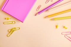 Libreta con los lápices y los clips de papel en fondo fotos de archivo
