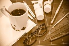 Libreta con los objetos inmóviles para las ilustraciones y el café caliente Foto de archivo