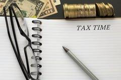 Libreta con palabras del tiempo del impuesto, el lápiz, los vidrios y los billetes de banco del dólar fotografía de archivo libre de regalías