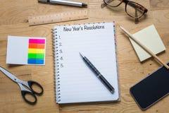 Libreta con resoluciones del ` s del Año Nuevo en el top y la lista debajo de los wi Foto de archivo
