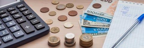 Libreta, cuentas, diverso dinero y una calculadora en la tabla fotos de archivo