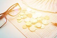 Libreta de banco del cuenta de ahorros, dinero tailandés, monedas, vidrios del ojo y lápiz en fondo azul Fotos de archivo libres de regalías