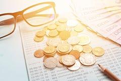 Libreta de banco del cuenta de ahorros, dinero tailandés, monedas, vidrios del ojo y lápiz en fondo azul Foto de archivo libre de regalías