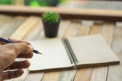 Libreta de la escritura de la inspección del negocio del hombre con el lápiz en la madera foto de archivo libre de regalías
