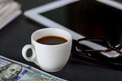 Libreta de la tableta, vidrios y taza de café del café express en el americano del efectivo de la oficina de los E.E.U.U. 100 dól fotos de archivo libres de regalías