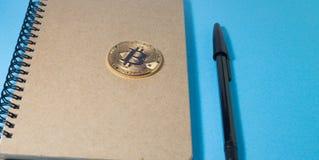 Libreta de madera, moneda de Bitcoin y dos plumas negras Fotografía de archivo libre de regalías