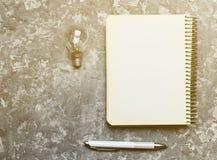 Libreta del inconformista, pluma y bulbo incandescente en una tabla concreta Foto de archivo